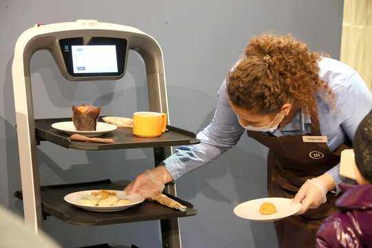 A waitress puts plates on a tray of a robot waite