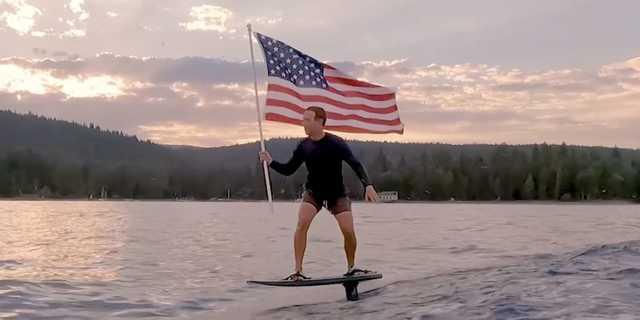 アメリカ国旗を手に電動サーフィンをするフェイスブックCEOのマーク・ザッカーバーグ氏。フォーブスの2021年長者番付に載った最年少ビリオネア15人の中で、一番の資産家だ。