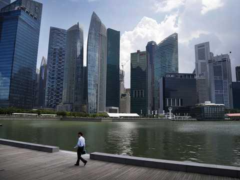 ランチタイムにシンガポールリバーフロントを歩くオフィスワーカー。