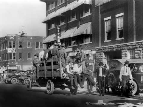 1921年6月、オクラホマ州タルサで人種虐殺が発生した際、兵士とアフリカ系アメリカ人を乗せたトラックが走っている。