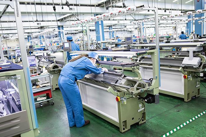 コンピューター横編み機を製造する作業員