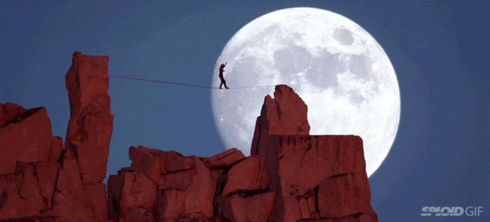 神秘な時間に息をのむ。巨大な月を背にして綱渡りをする男