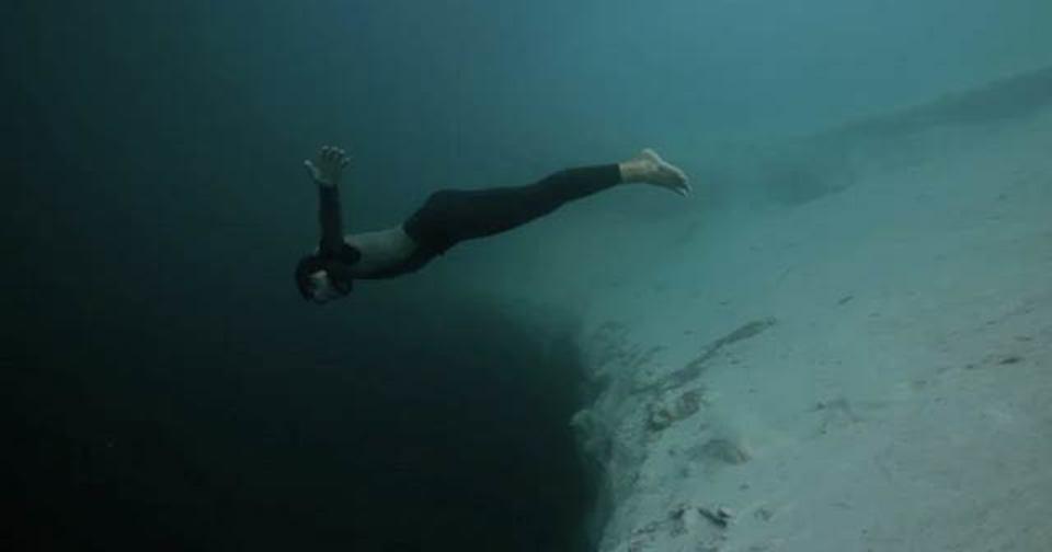 深く深くフリーダイビング...カメラが捉えた海底の巨大穴に潜り込んでいくダイバー