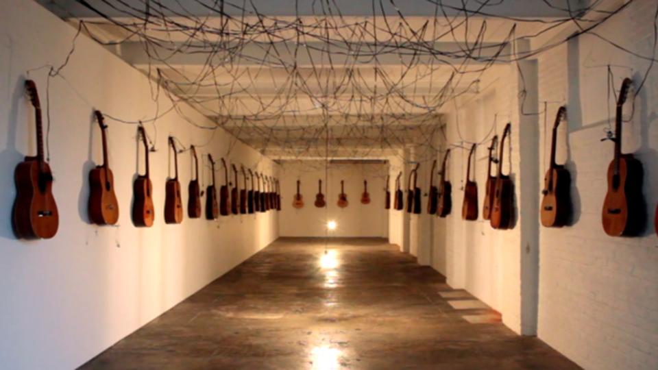 廊下に並べられた40本のギターが起こすイリュージョン