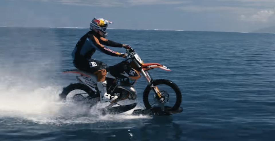 タヒチの大波をバイクでサーフィンする人