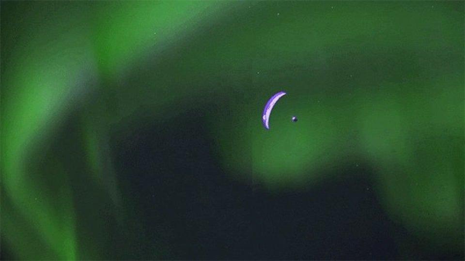 オーロラを背景にパラグライダーが飛ぶ姿が、現実感がないほど美しい