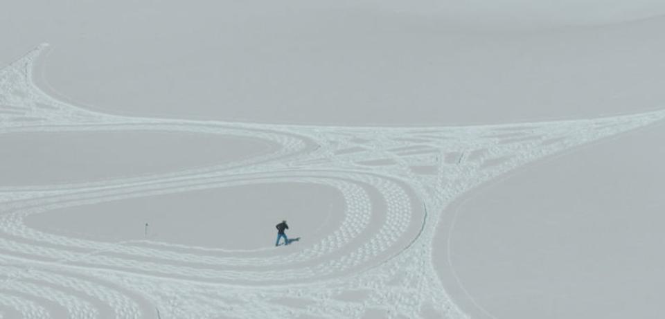 靴がペン、雪がキャンパス。雪の中を歩いてデザインする男