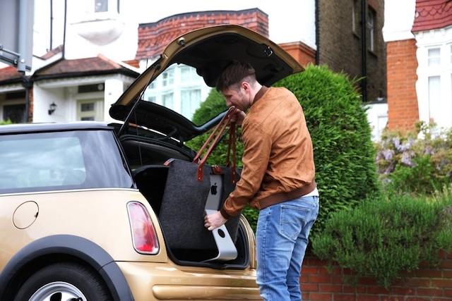 iMac専用バッグを車に積む男