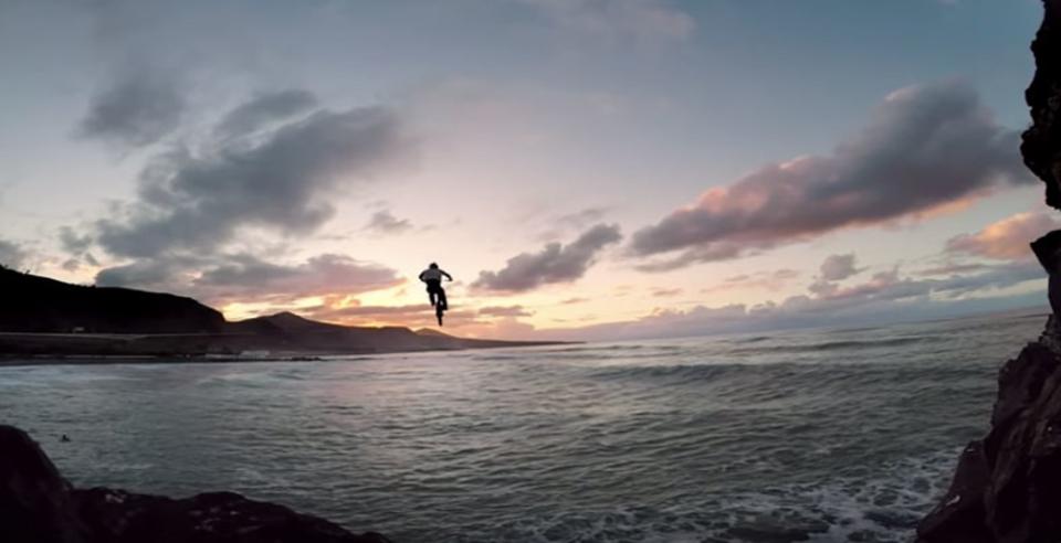 計算されたスタントと言われても怖い、崖の上の路地裏からチャリで海にジャンプ