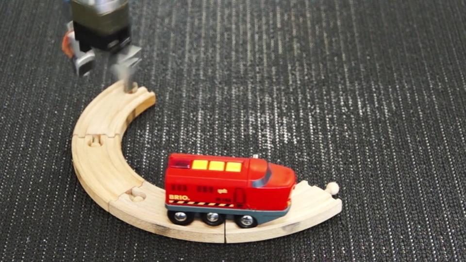 無限に周回する玩具の電車と、足りない線路を置き直すロボット・アームに人生を感じてみよう