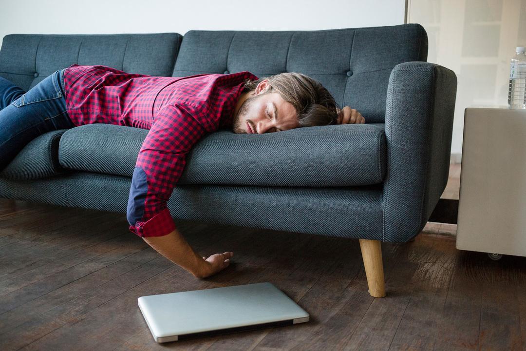 ソファーで寝る若い男性とノートパソコン