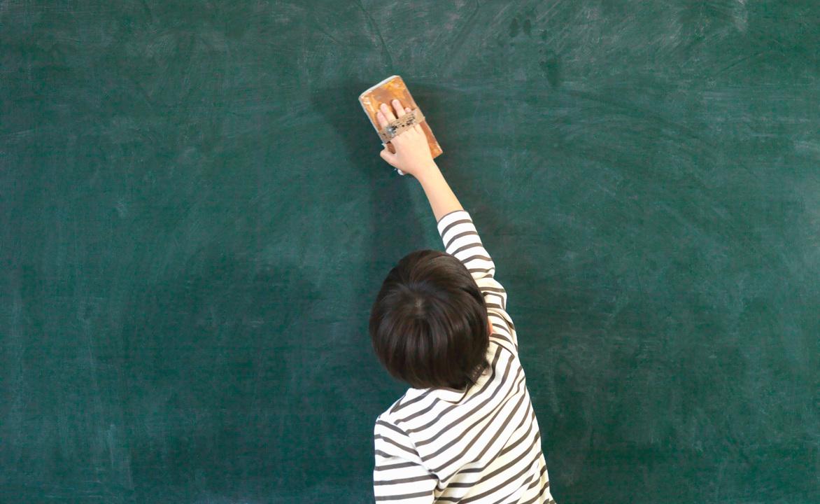 教室の黒板を掃除する子ども