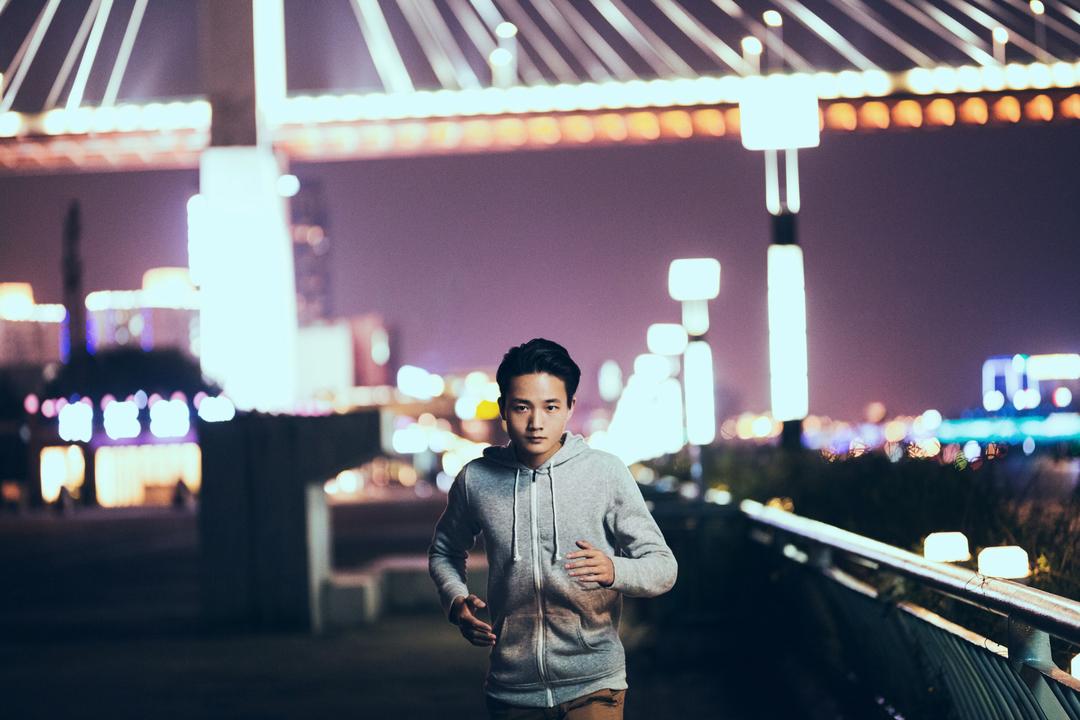 夜、橋の下を走る男性