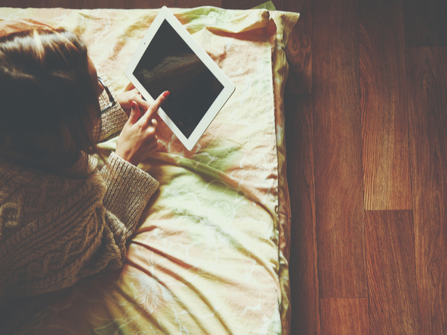 ベッドの上でタブレットをさわる女性