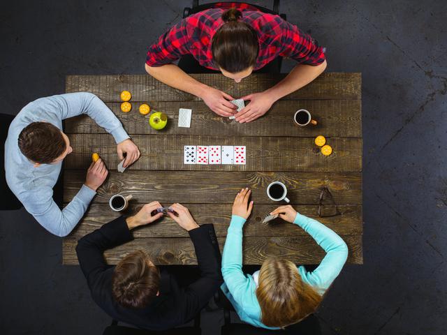 テーブルでトランプをする4人組