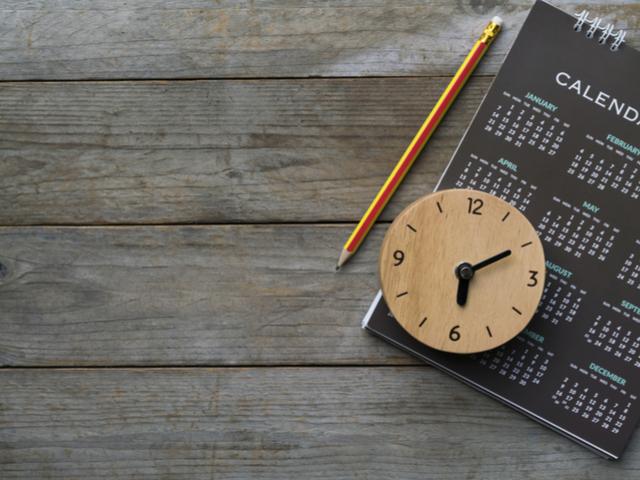木製テーブルの上にあるペンと時計とカレンダー