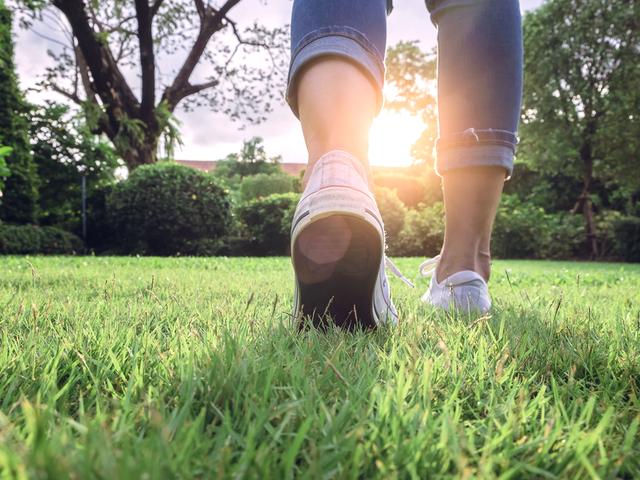芝生の上を歩く女性の足元