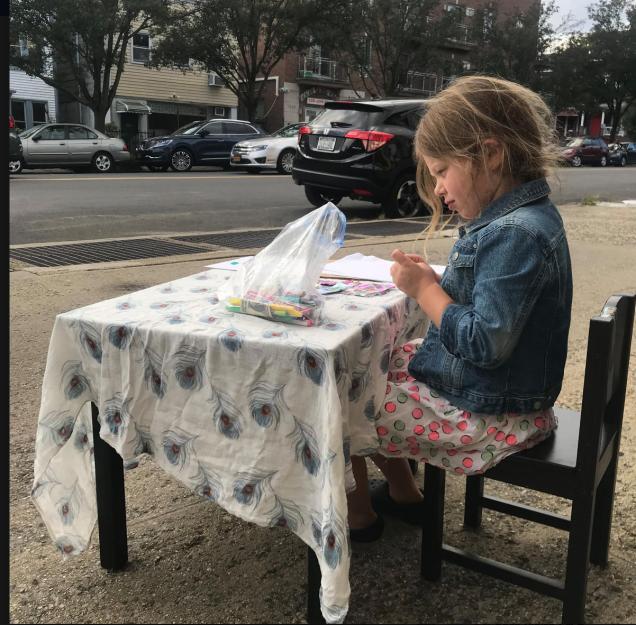 道端にあるイスとテーブルに座る少女