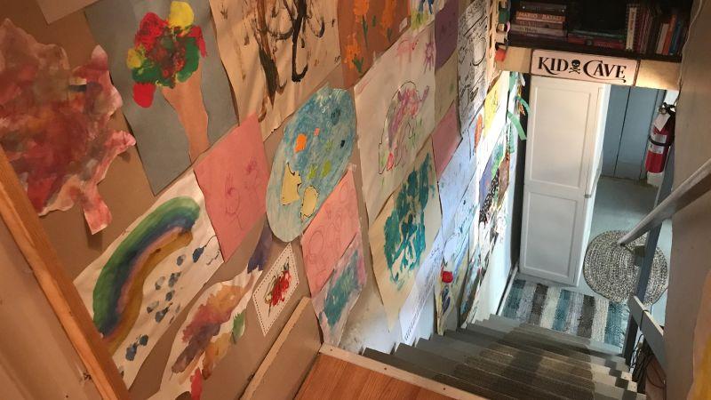 地下室に続く階段の壁に子どもの絵がたくさん