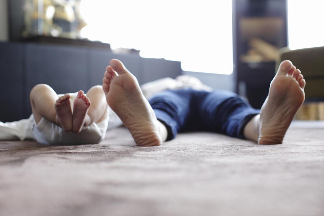 リビングで寝っ転がる赤ちゃんとお母さんの足