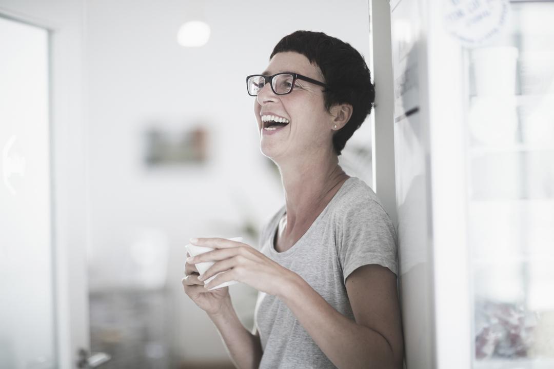 笑いながらコーヒーを飲む女性