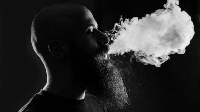 たばこの煙を吐き出す男性