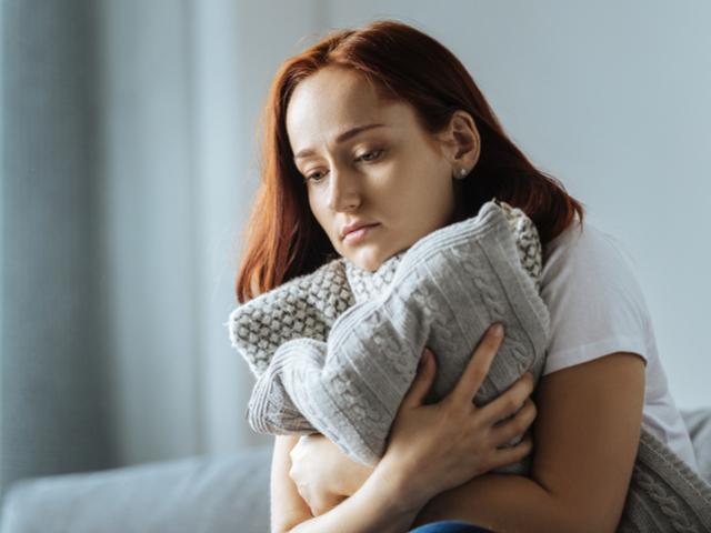 枕をかかえる女性