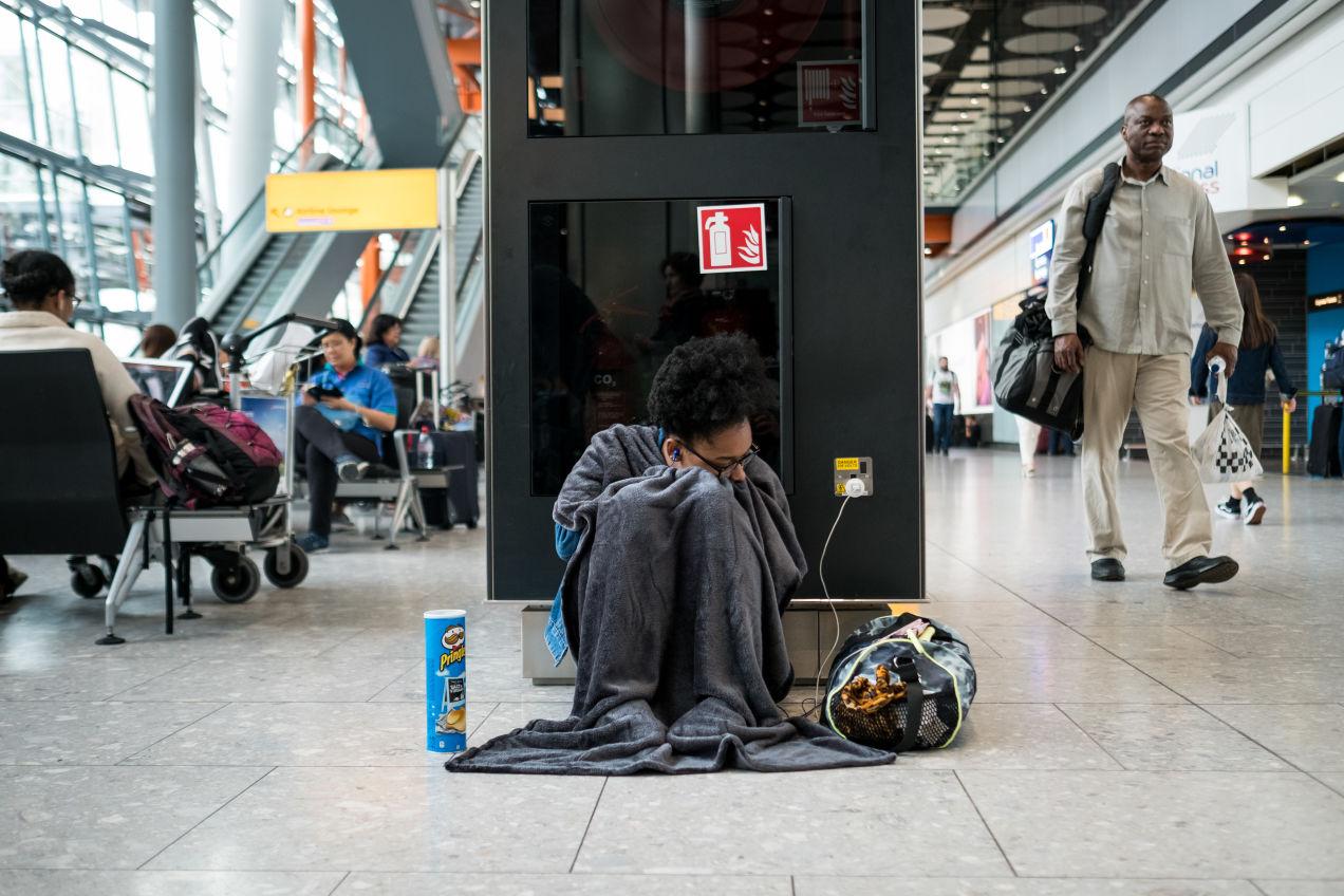 空港の床に座り込む男性