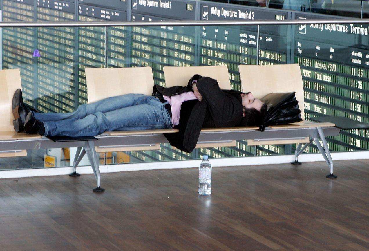 空港のベンチで寝る男性