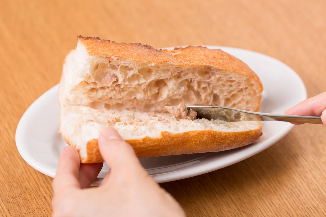フランスパンにバターとレバーペーストを塗る