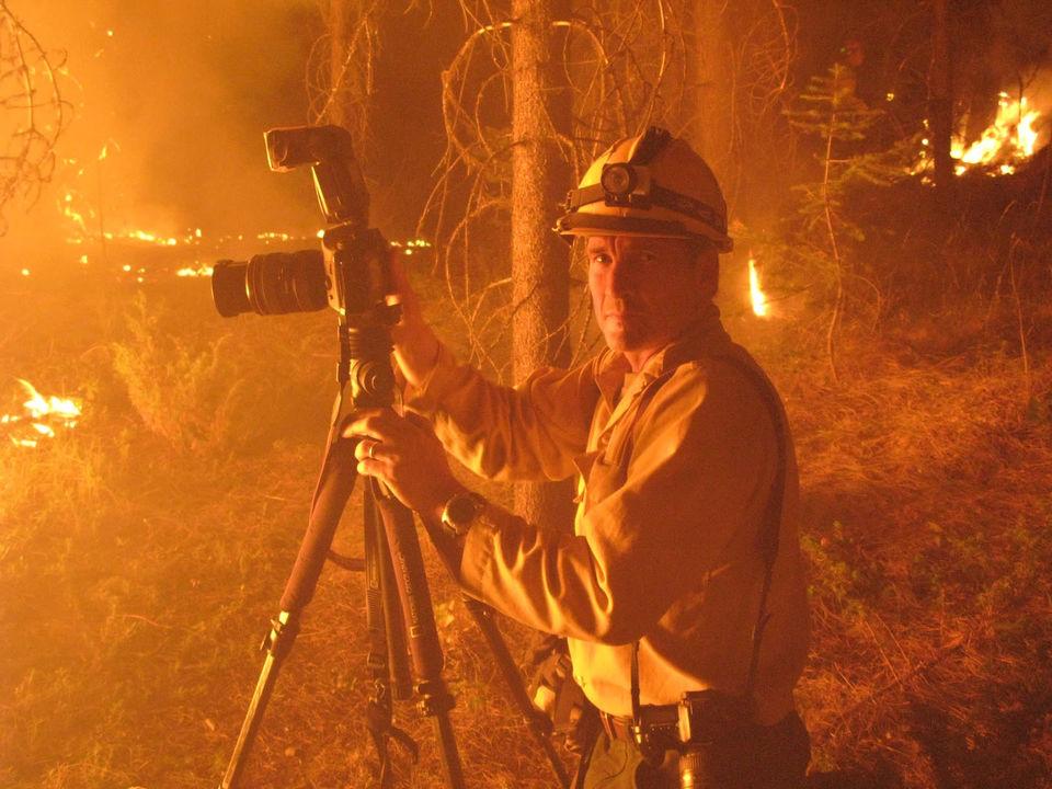 火事現場でカメラをかまえる男性