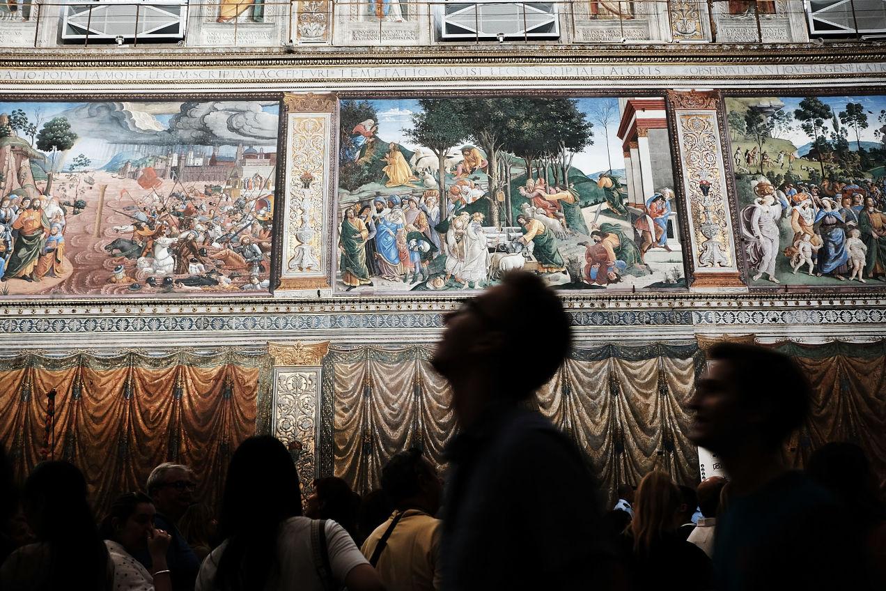 美術館の絵を見て歩く男性