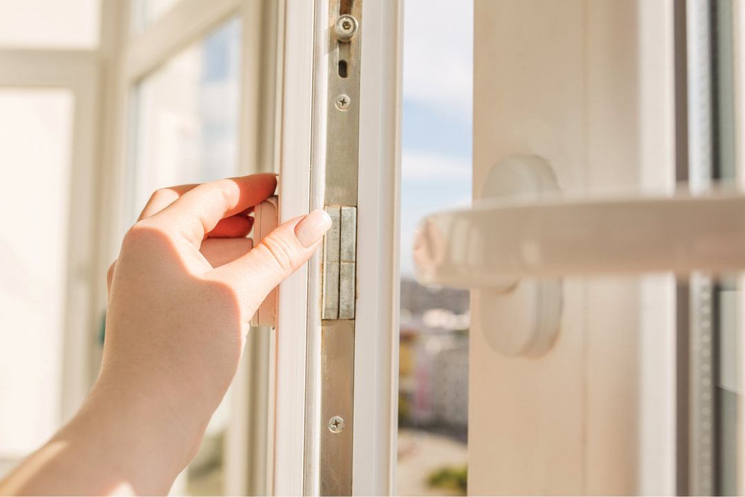 窓を開けて換気する女性の手