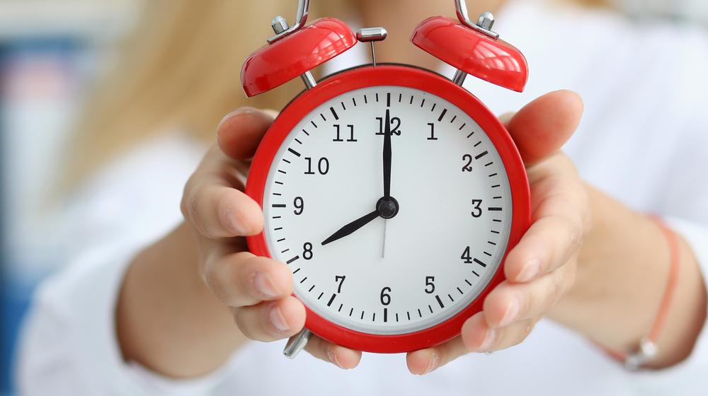 時計を手に持つ女性