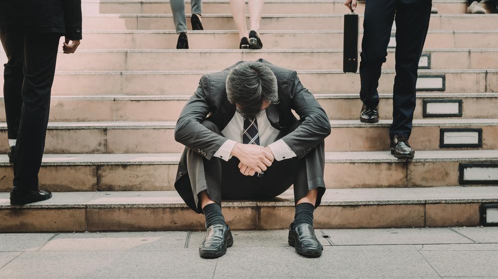 階段で座り込み落ち込む男性