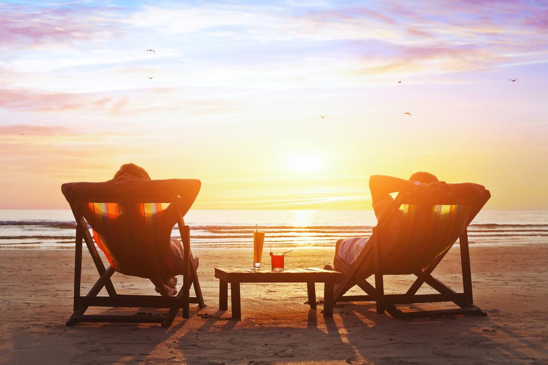 浜辺で夕日を眺めるカップル