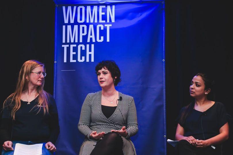 垂れ幕の前に座る3人の女性