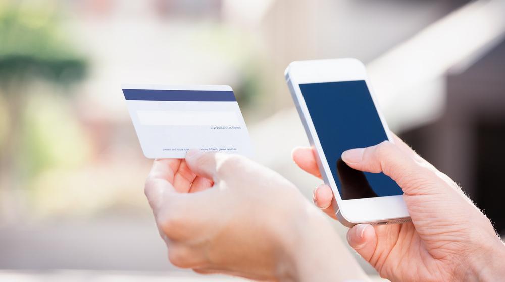 クレジットカードとスマホを持つ手