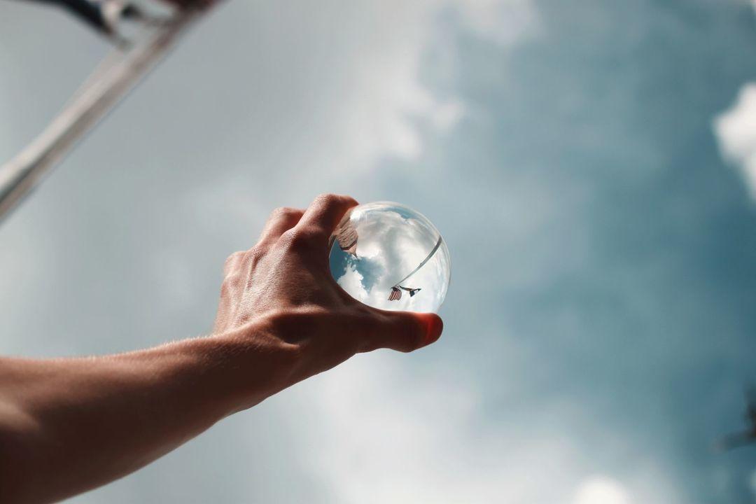 空にかざしたガラス玉