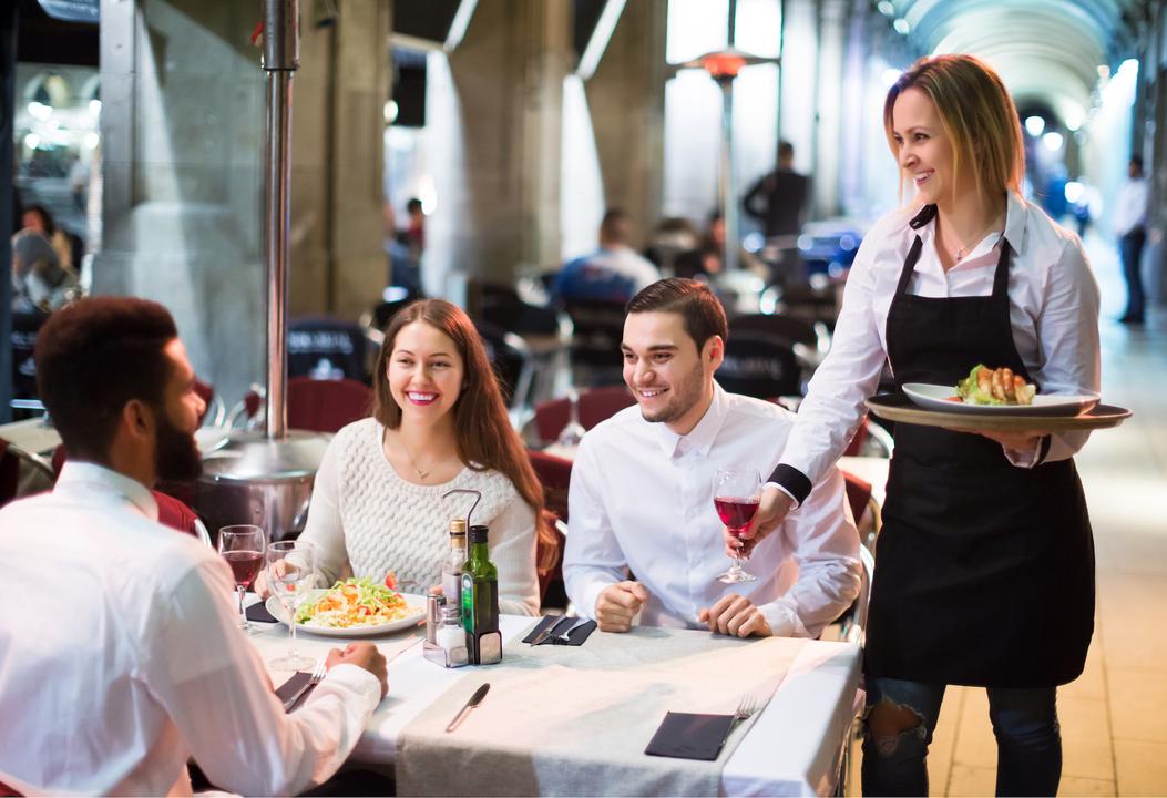 レストランで食事をする会社の同僚たち