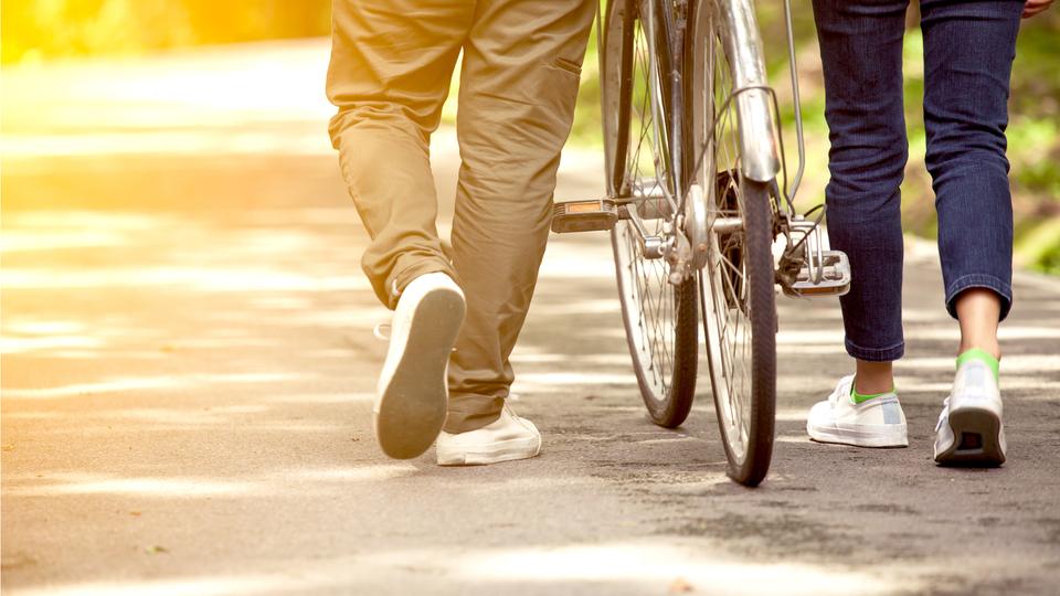 カップルが自転車を押す後ろ姿