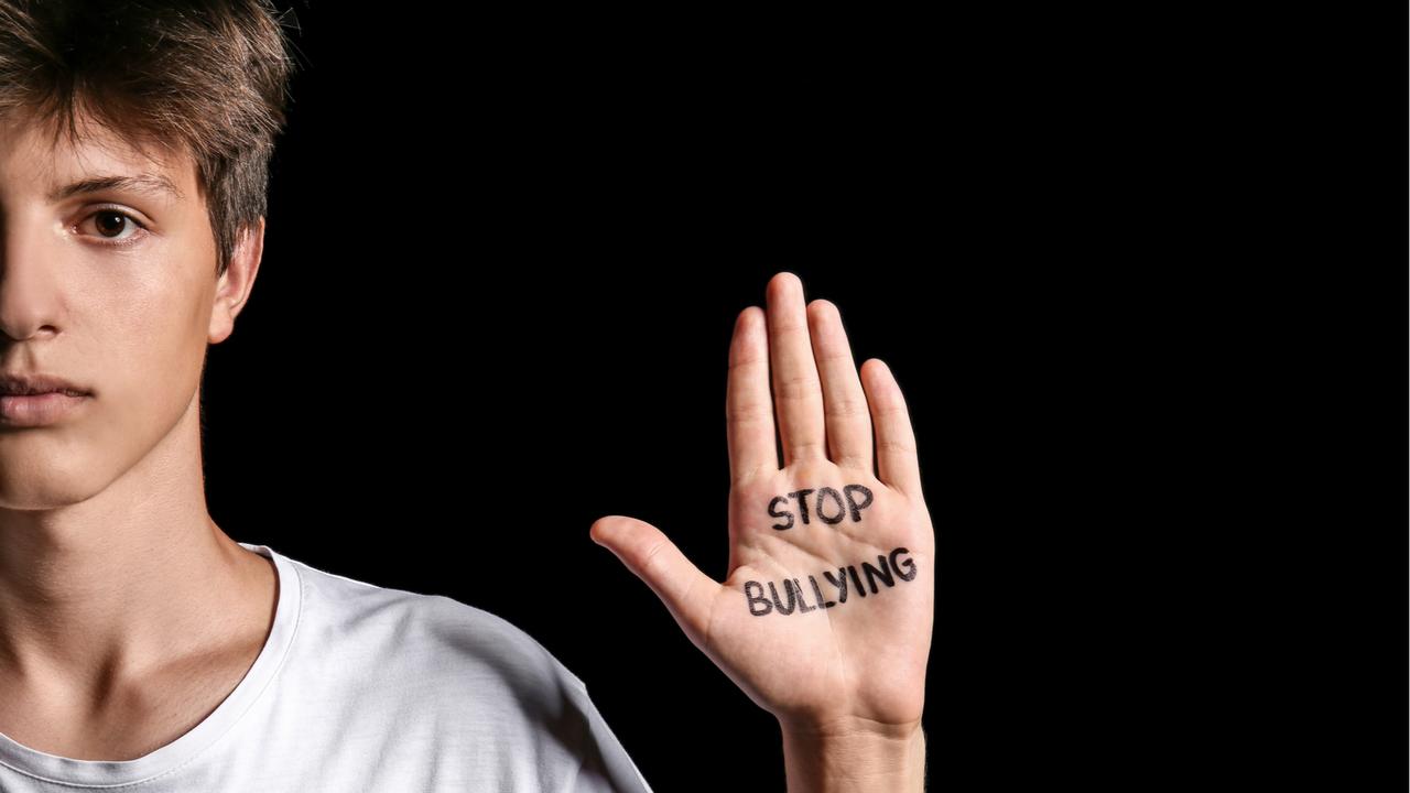いじめをやめようと手を掲げる青年