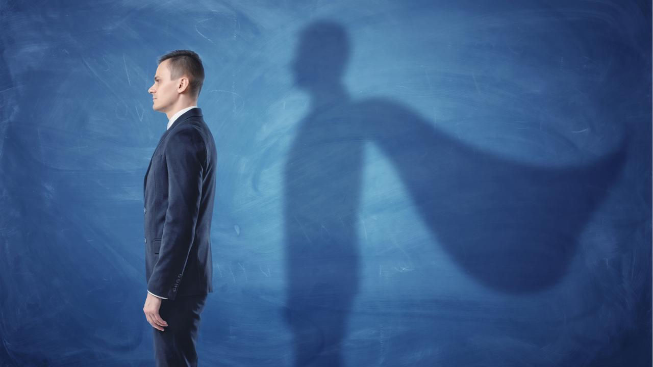 ビジネスマンとスーパーヒーローの影