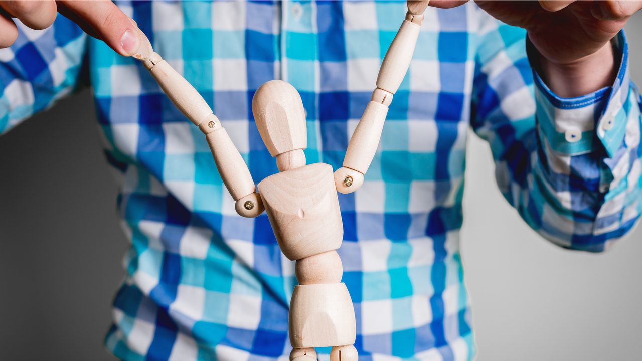 男性が人形を持っているところ