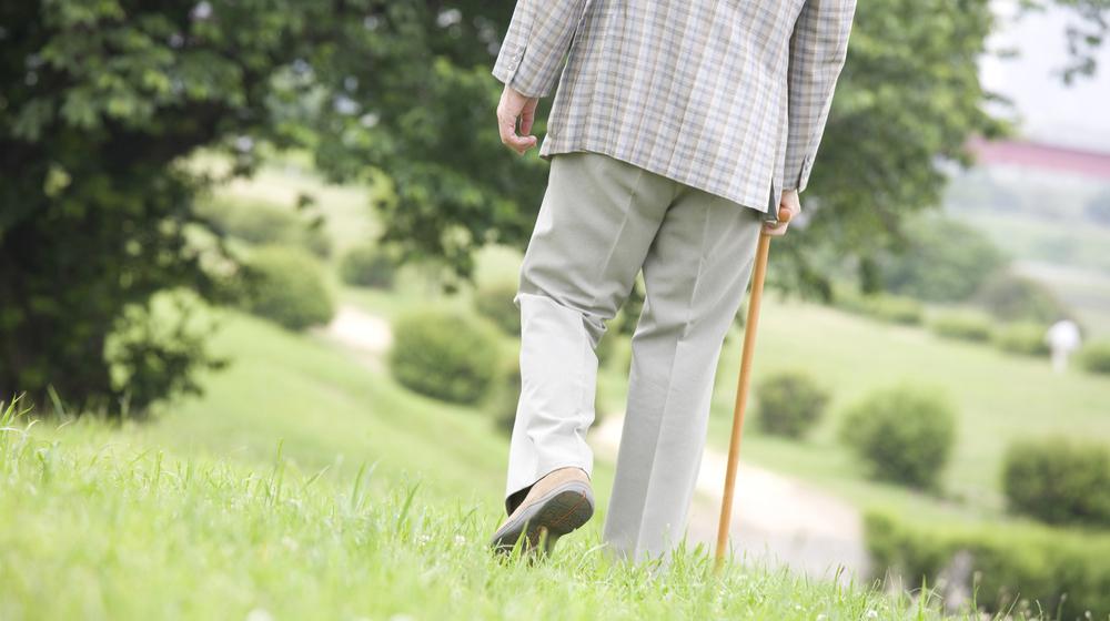 杖をついて歩く男性の後ろ姿