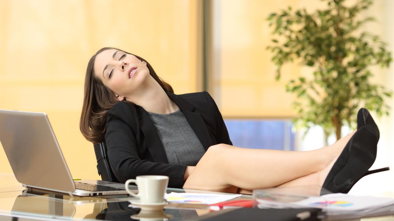 机に足をのせて眠る女性