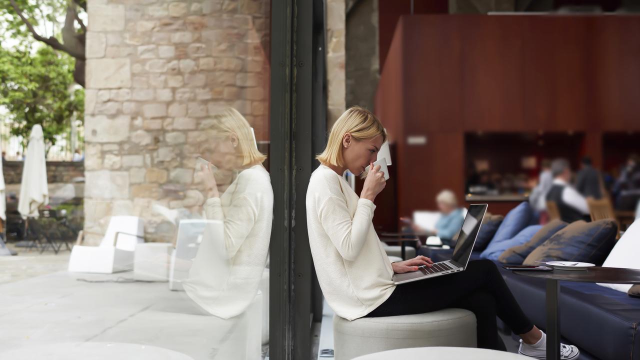 カフェの窓際で仕事する女性