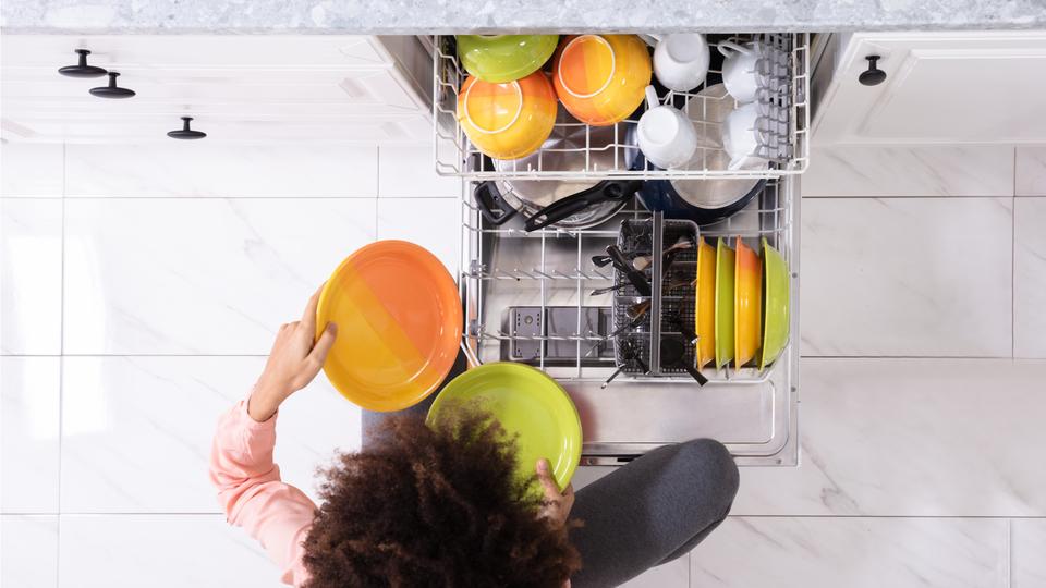 食洗機にお皿をいれる女性