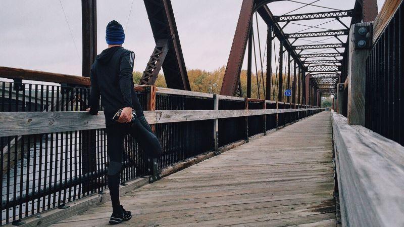 橋の上でストレッチする男性