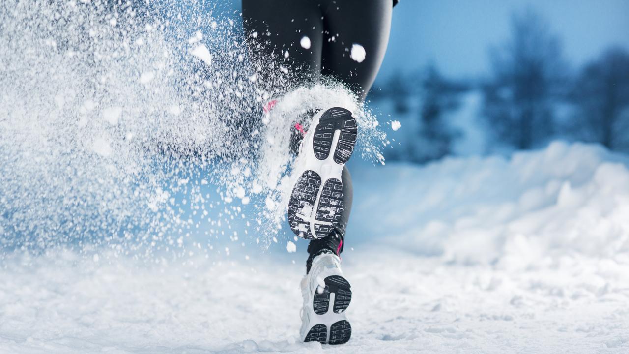 雪の中を走る女性
